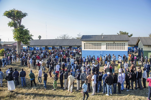 Zambian voters queue up in long lines to cast their ballots at a polling station in Lusaka on August 12, 2021. - Zambians were voting in a general election on August 12, after a tense campaign dominated by economic woes, a debt crisis and the impact of the coronavirus